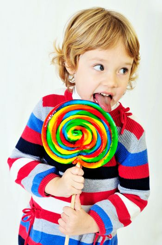 little girl licking big colorful lollipop