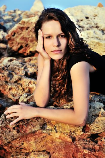brunette girl laying on the cliff at sunset time