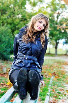 lovely teen girl sitting on the bench in autumn park