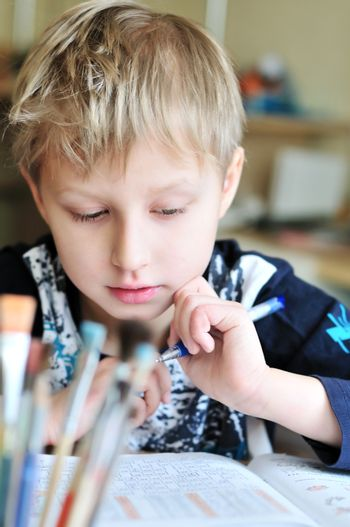 left-handed boy doing a home task at home