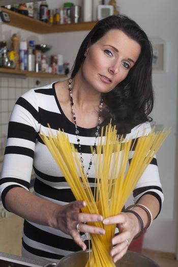 woman cooking spaghetti in the kitchen