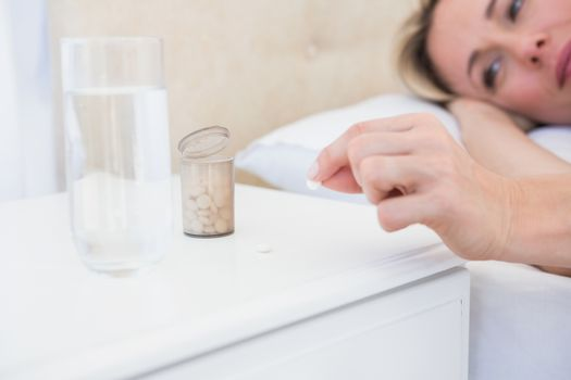Pretty blonde lying bed taking pills on bedside table