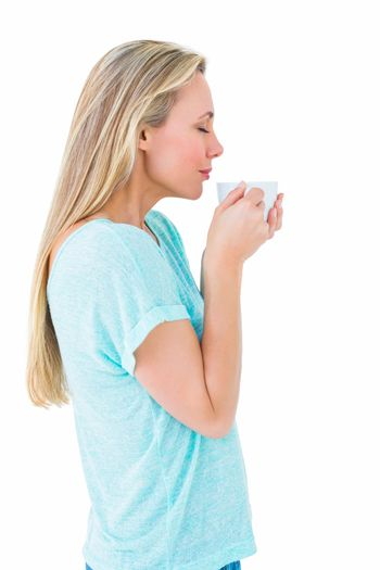 Pretty blonde standing and holding hot beverage