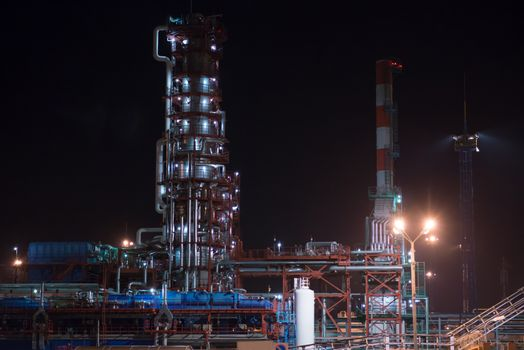 Industrial area refinery. Distillation column and pipes. Night view
