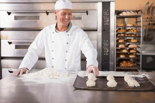 Baker putting dough on baking tray