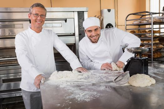 Smiling baker kneading dough next to his colleague in the kitchen of the bakery