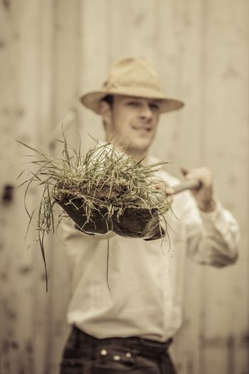 Farmer with a Shovel Full of Grass. Focus on the Grass