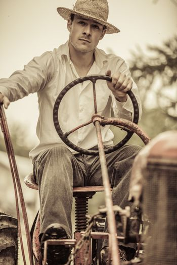 Young Farmer Driving a Red Old Vintage Tractor