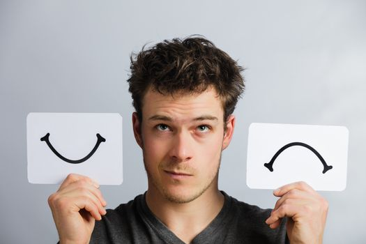 Portrait of a Questioning Man Holding Happy and Unhappy Survey Mood Board