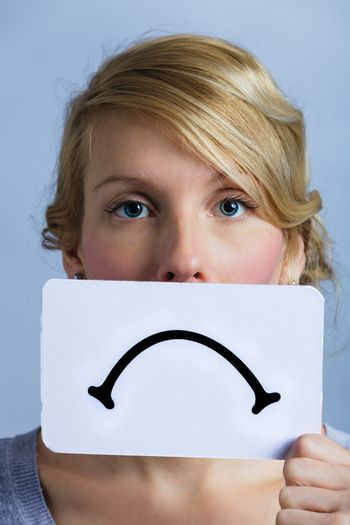 Unhappy Portrait of a Woman Holding a Sad Mood Board with Blue Background