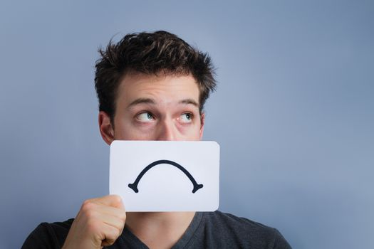 Unhappy Portrait of a Man Holding a Sad Mood Board with Blue Background