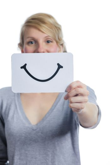 Happy Portrait of a Woman Holding a Smiling Mood Board Isolated on White Background