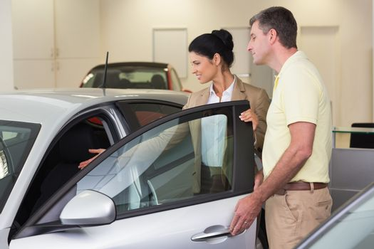 Businesswoman showing a car interior to her customers