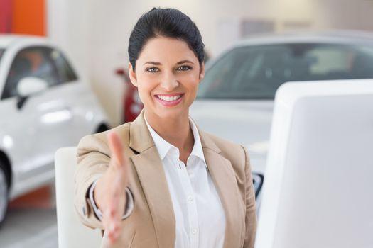 Smiling businesswoman reaching for handshake