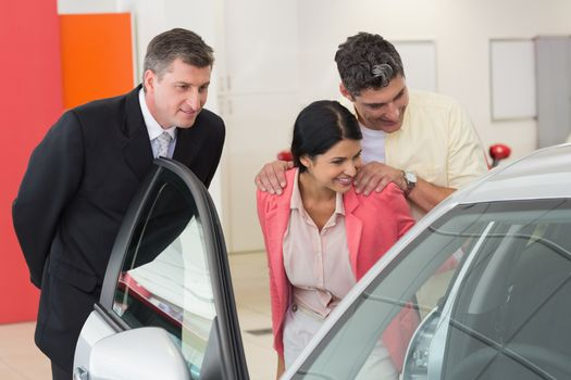 Car dealer showing the interior of a car to a couple