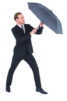 Businessman holding umbrella to protect himself
