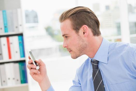Focused businessman text messaging