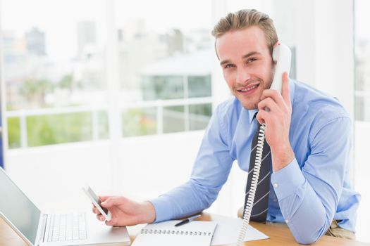 Businessman on the phone while text messaging