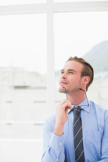 Businessman holding glasses in day dreaming