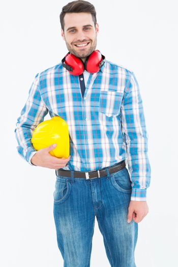 Confident manual worker with hardhat and ear muffs