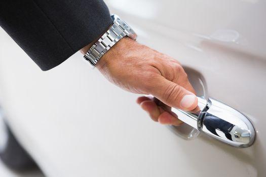 Man holding a car door handles