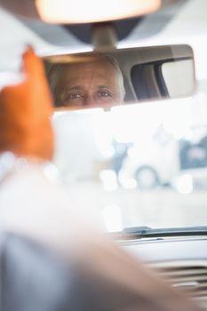 Businessman looking in an interior car mirror