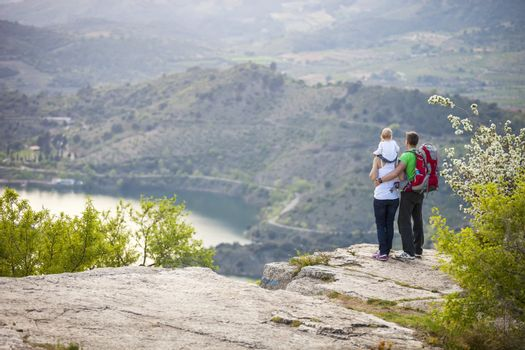 Young couple with toddler boy standing on cliff