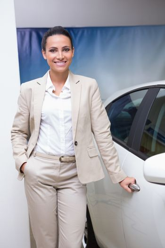 Smiling businesswoman holding a car door handles