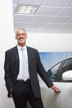 Smiling businessman holding a car door handles