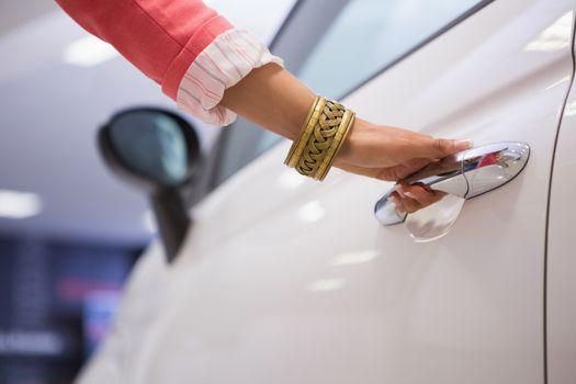 Woman holding a car door handles