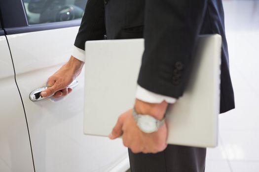 Man holding a car door handles with a laptop