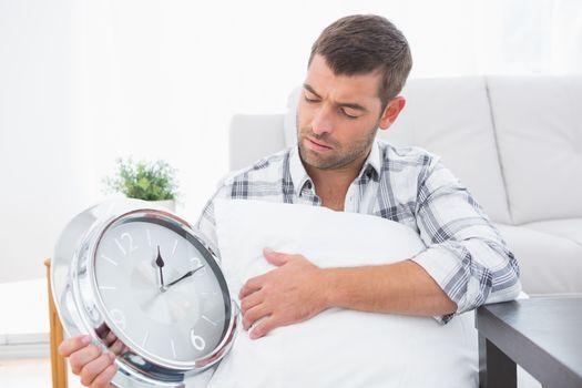 Anxious man beside a clock