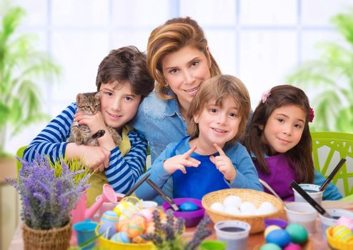 Family portrait in Easter time, creative mother with three cute adorable child coloring eggs, making vibrant colorful traditional food