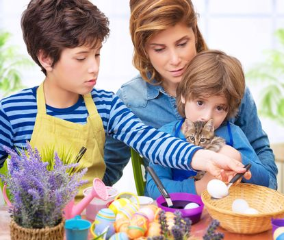 Happy family paint Easter eggs at home, mother with two adorable sons and cute cat make traditional Easter decorative food