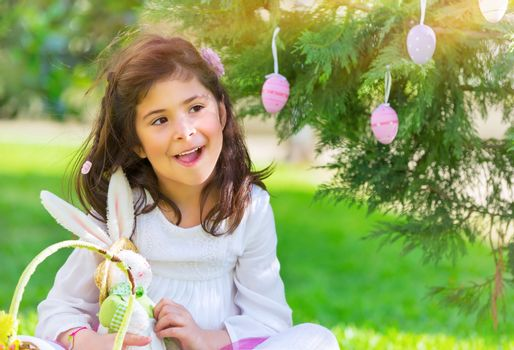 Portrait of nice little girl playing traditional Easter game, happy egg hunting, having fun at spring park in religious holiday