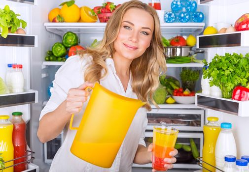Happy woman pouring juice