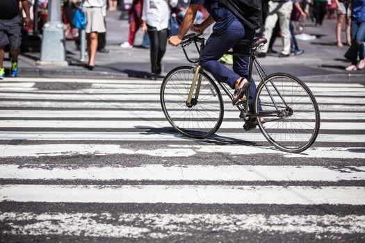 Man on a bike on a crossing in Manhattan, NYC