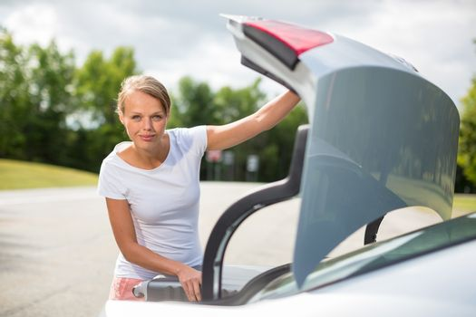 Young, attractive, happy woman taking a suitcase from her car's