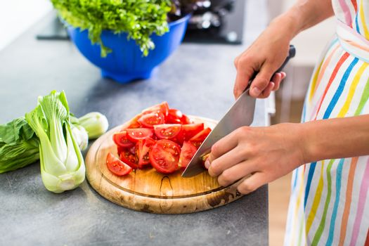 Young woman cutting vegetables in her modern kitchen