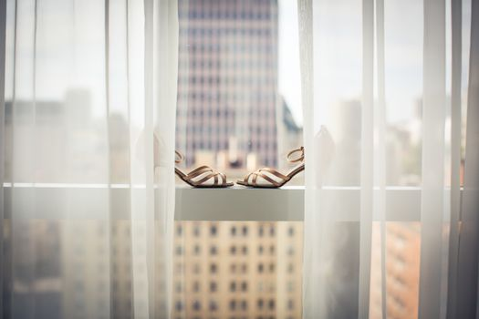 Lovely fashionable shoes of a bride on a window