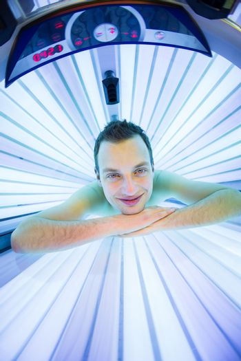 Handsome young man relaxing  in a modern solarium