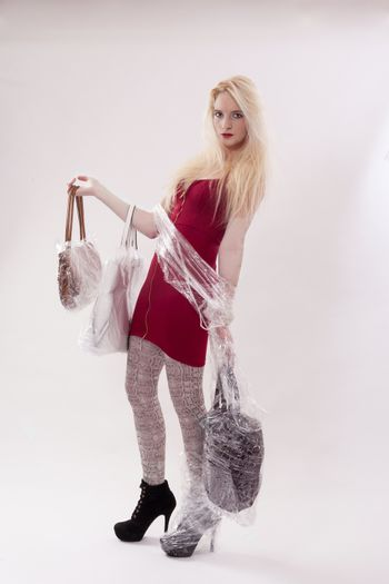 Young woman with long blonde hair in a red mini dress. She has three handbags in hand wrapped with plastic wrap. and your right foot is wrapped in packaging film. - Studio shot against white background.