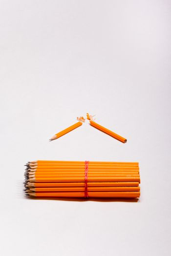 yellow pencils and a broken pencil on gray background