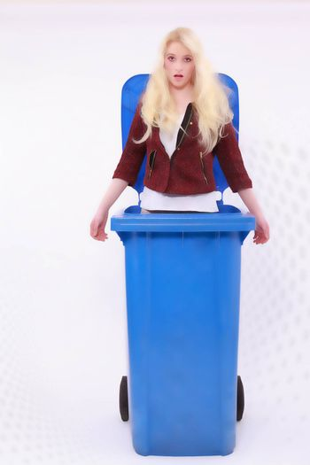 Young blonde long-haired girl, fashionable dressed standing in a blue Garbage containers with serious facial expression. light pattern in the background.