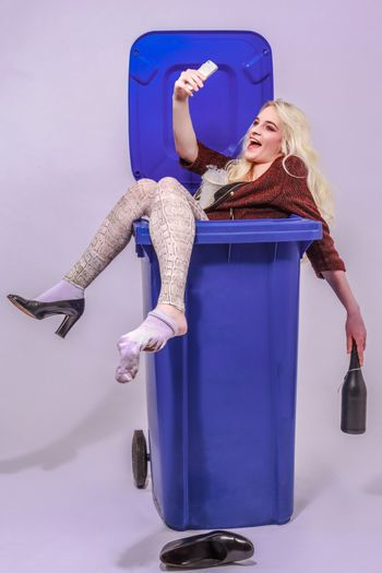 Young alcohol-impaired girl with long blond hair sitting laughing in a blue garbage can and makes your smartphone a Selfie. - Studio Recording.