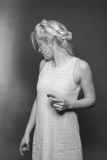 Blonde girl in mini dress made of lace and stylish hairstyle with biscuit in hand looks backwards. Black and white image, studio shot.