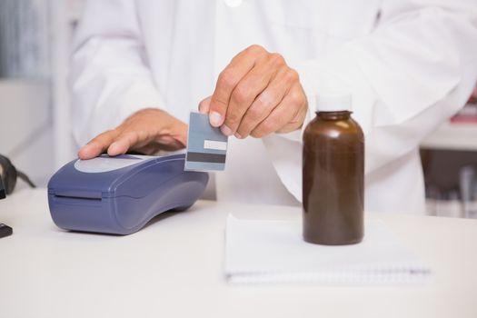 Pharmacist using keypad with credit card