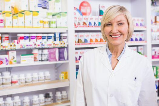 Smiling blonde pharmacist posing in lab coat