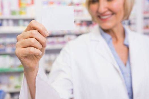 Smiling pharmacist showing calling card