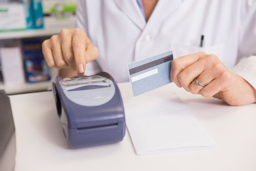 Pharmacist using keypad and holding credit card